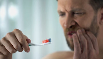 A man feeling the pain of gum disease. Learn more about gum disease. What is it? How to precent it.