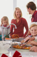 Family around the kitchen while grandmother cuts holiday food